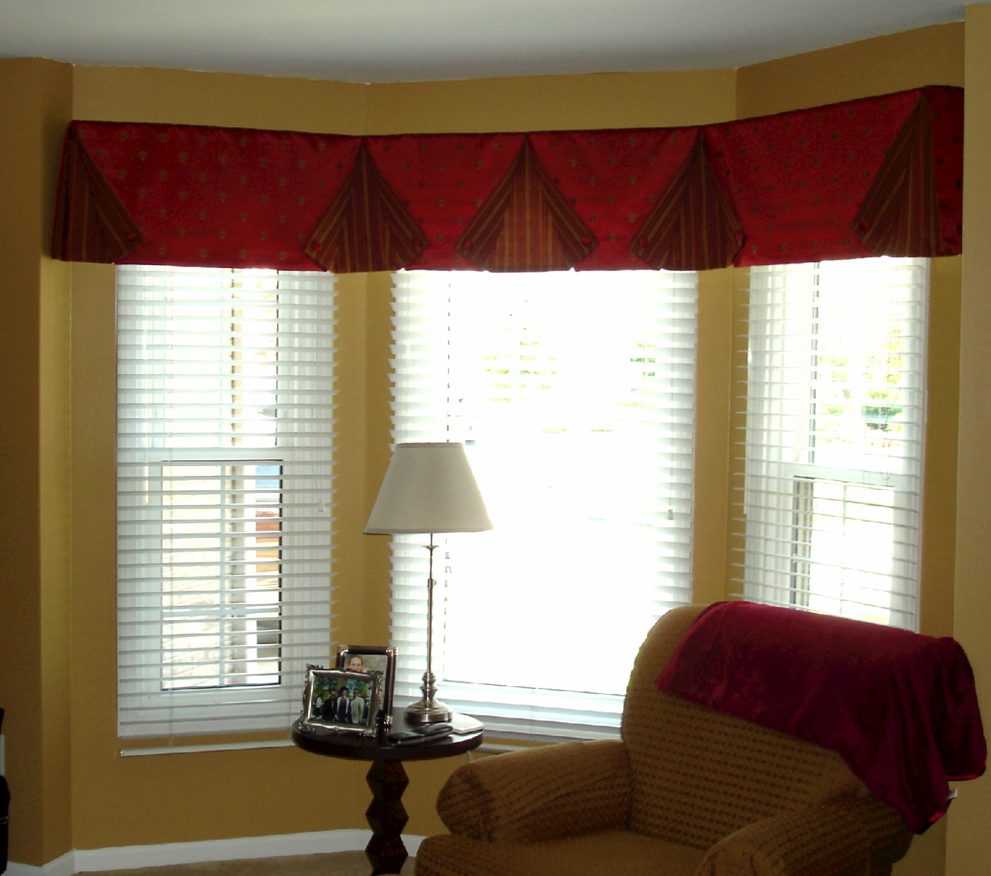 Cornice features a button back valance angled with the bay for Window valance